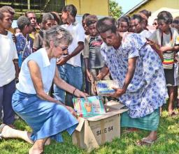 Maureen Hill and a teacher from the Holy Cross Merio Primary School opening on of the boxes of books