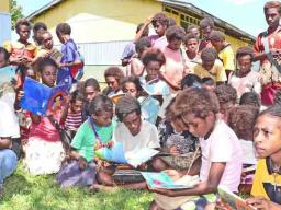 Excited children with donated books.