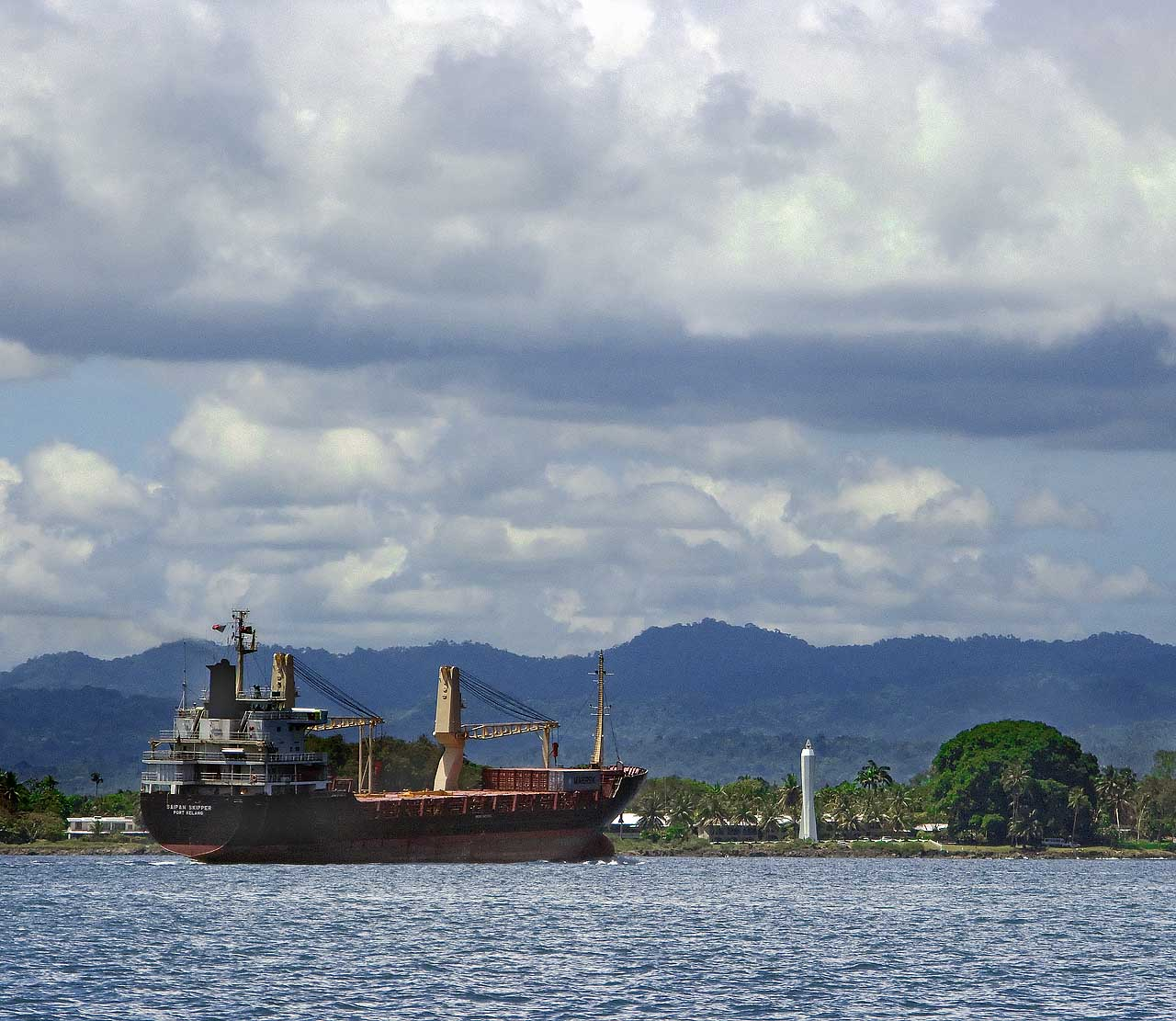 A cargo ship passes the Coastwatchers Monument in Madang