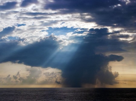 The morning sun sends rays through a rain cloud over Astrolabe Bay