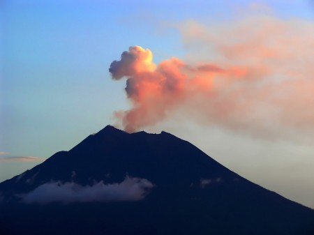 The red light of sunset lights up the eruption of Manam Island volcano