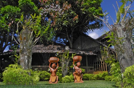 Two spirit figures in an orchid garden at Madang Lodge