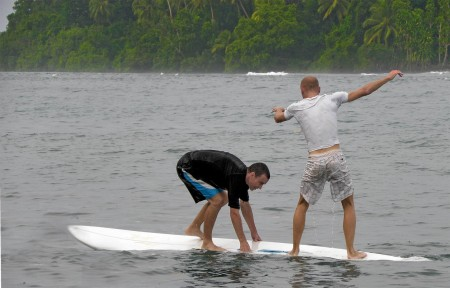 Two fools trying to stand on a sailboard
