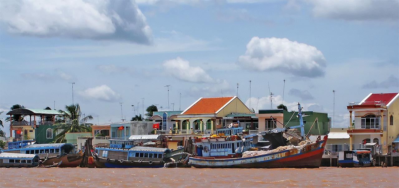 Boats and beautiful houses line the banks of the Mekong River